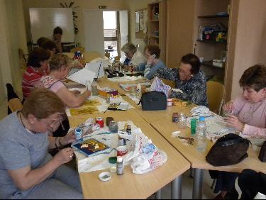 Varias personas mayores realizan trabajos compartiendo una gran mesa en el aula de manualidades
