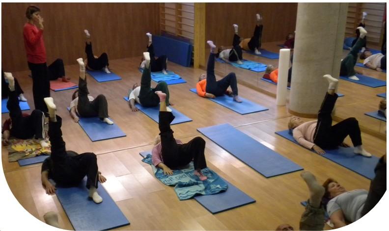 Foto con personas  mayores haciendo ejercicios sobre las colchonetas